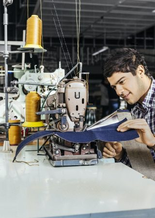 Side view of tailor sewing jeans in factory